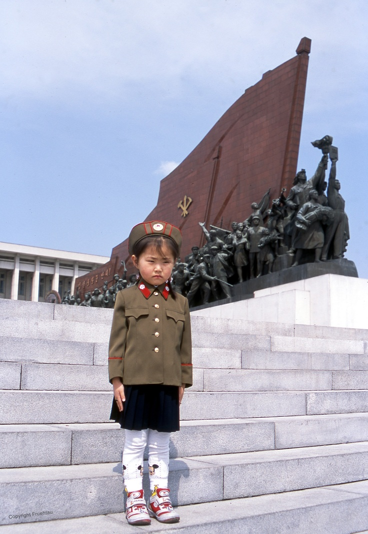"A young girl standing at the steps up to Mansu Hill, North Korea. The Grand Monument on Mansu Hill is a complex of monuments in Pyongyang, North Korea. There are two monuments showing many different soldiers, workers, farmers, and so on; ""Anti-Japanese Revolutionary Struggle"" and ""Socialist Revolution"". These memorials are 22.5 meters high . and 50 meters long. The long line of human figures depicted on them are on average 5 meters high."