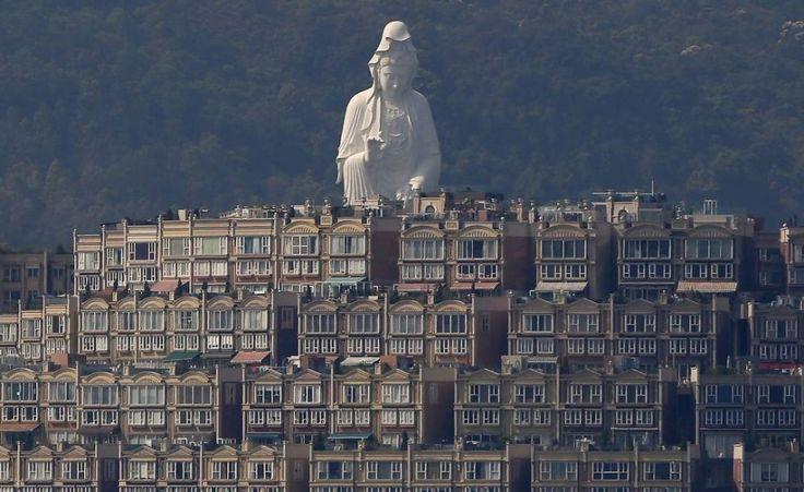 La statua buddista di Avalokiteśvara, divinità della compassione, alta 76 metri, è parte del monastero di Shan Tsz e si trova dietro le case di lusso del distretto di Tai Po, a Hong Kong (Reuters/Bobby Yip)