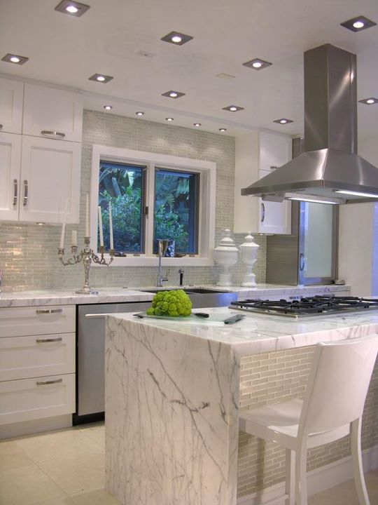 White Carrera marble kitchen. Love the marble and the glass tiles but strongly dislike the ceiling cannister lights.
