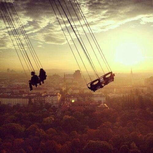 swings hanging over a city sun set