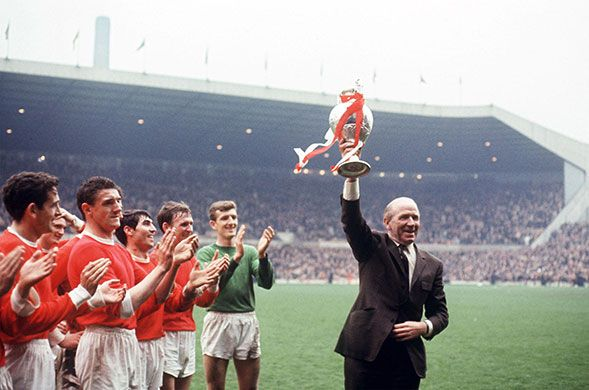 Manchester United manager Matt Busby holds the League Championship trophy aloft as Shay Brennan, Bill Foulkes, Tony Dunne, Pat Crerand, Alex Stepney celebrate Manchester United's 1967 triumph