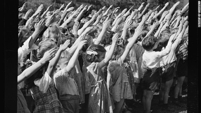 """Before 1942, American children pledged allegiance to the flag with the Bellamy salute.  (Francis Bellamy wrote the pledge.) Worried that it might be confused with the Nazi's Roman salute, Congress changed the salute to simply placing a hand over the heart. Also of interest is the fact that the phrase """"under God"""" was not added until 1954."""