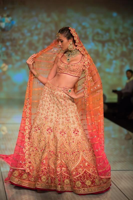 Tarun Tahiliani orange peach bridal wedding lehnga. More here: http://www.indianweddingsite.com/bmw-india-bridal-fashion-week-ibfw-2014-tarun-tahiliani-show/