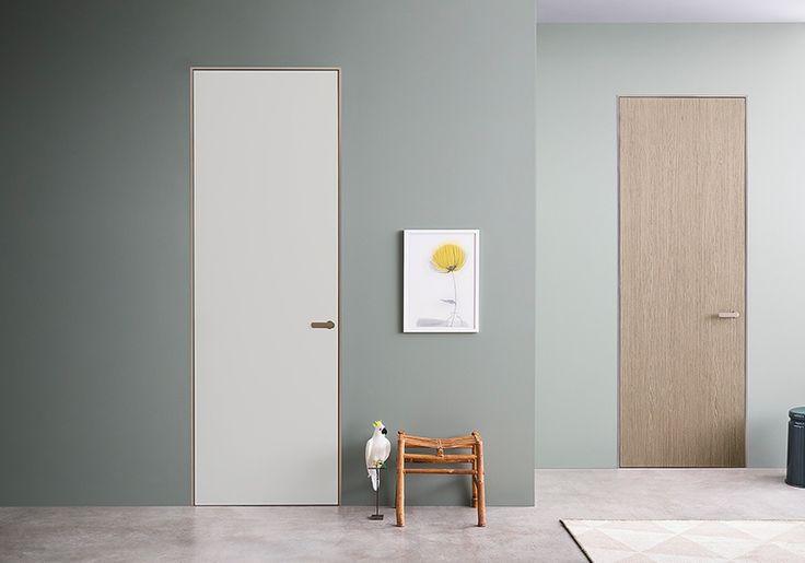 Porta a battente perfettamente integrata con la parete e l'architettura circostante. Segna il passaggio da un ambiente all'altro indossando finiture diverse.