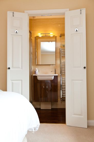 Wardrobe becomes an En-suite:  The owner converted a small walk-in wardrobe, into a compact en-suite bathroom. The slim-line doors were ingeniously created by splitting and re-edging the existing door.