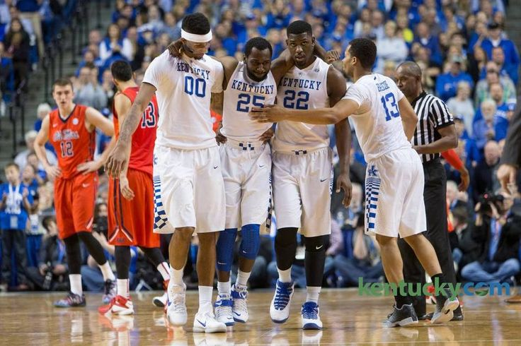 Kentucky forward Marcus Lee, left, and forward Alex Poythress help guard Dominique Hawkins off the court after he injured his ankle in the second half. The University of Kentucky hosted Ole Miss, Saturday, Jan. 02, 2016 at Rupp Arena in Lexington.