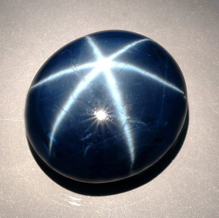 Star sapphire. From the corundum family. Contains unusual tiny needle-like inclusions of rutile. Aligned needles that intersect each other at varying angles produce a phenomenon called asterism.