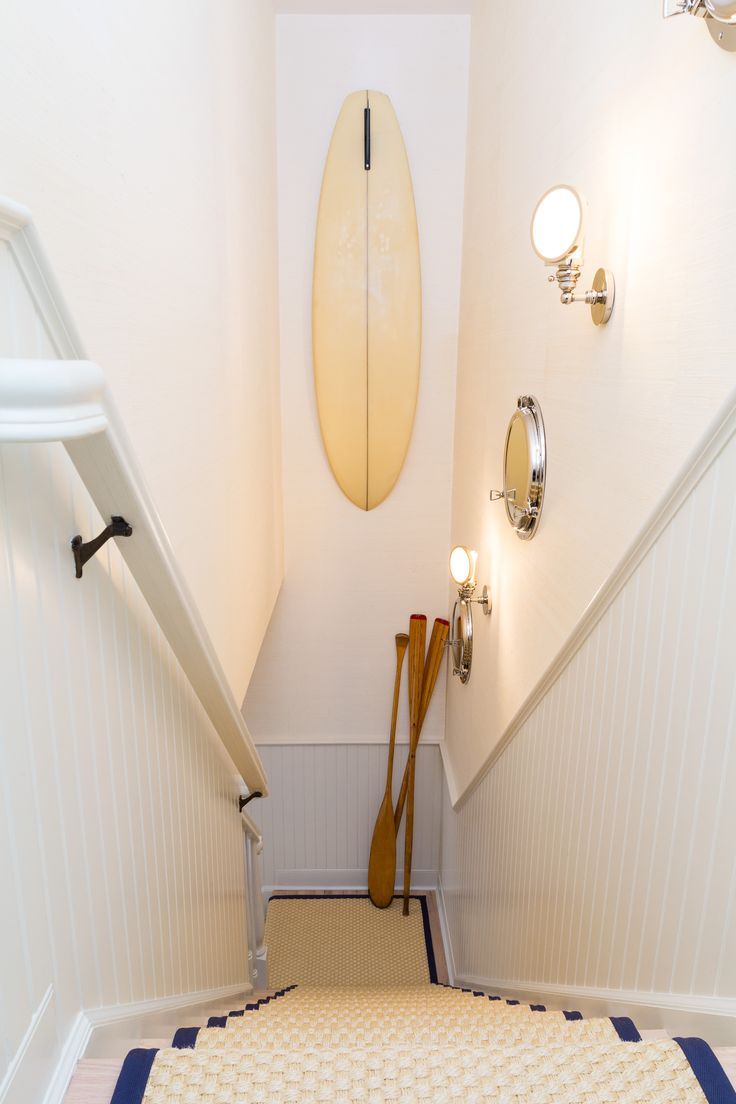 Hallway gallery to the home's second floor. Displayed is a vintage surfboard, nautical sconces and mirrors, and a collection of vintage oars. Custom sisal runner with navy blue binding adorn the bleached oak stairs. by Chango & Co.