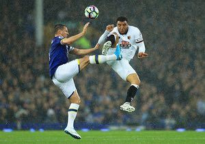 Phil Jagielka and Troy Deeney challenge for a high ball.
