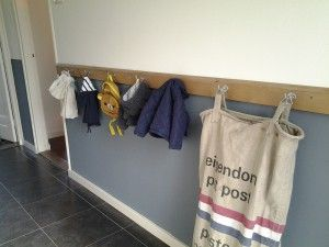 Lange lat met haken voor de jassen van de kinderen.