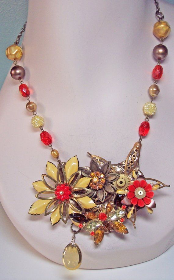 Rhinestone Butterfly Steampunk Statement OOAK Necklace. This statement necklace features a large vintage mustard gold flower layered with brass and topped with a plastic paprika color flower repurposed from an antique Czech pin. An old pocket watch gear is tucked in place as the center of an intricate brass flower. Another brass flower has an amber rhinestone center, also from a vintage Czech pin. A vintage plastic flower sits upon yet another enamel sprout with a smaller watch gear in the…