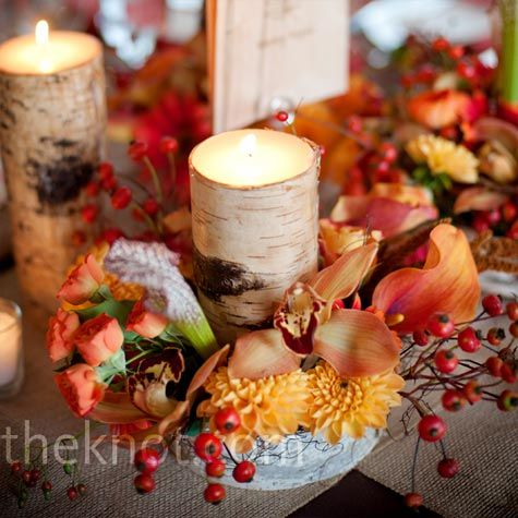 For a rustic look, the centerpieces included birch-bark containers and votive candles surrounded by a mix of orange and red flowers.