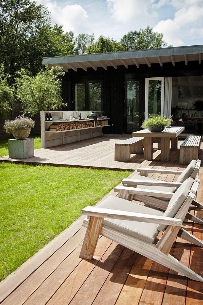 Stor veranda med utomhus kök, matplats och solstolar i naturmaterial
