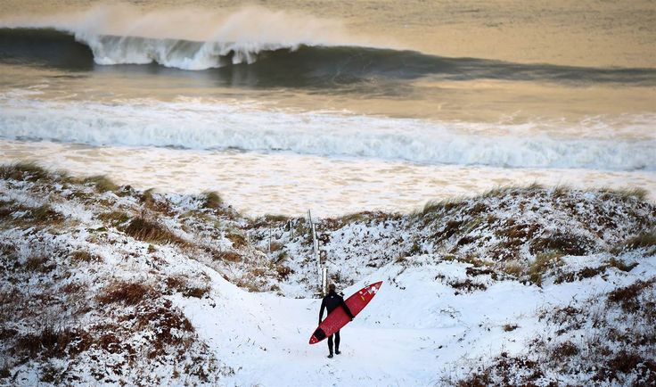 Charles McQuillan / Getty Images 10 Pro surfer Alastair Mennie makes his way towards the beach at Portrush on Jan. 14 in Antrim, Northern Ireland. The province experienced heavy snowfall as a cold weather front hit the northern part of the United Kingdom causing major traffic disruption and school closures.