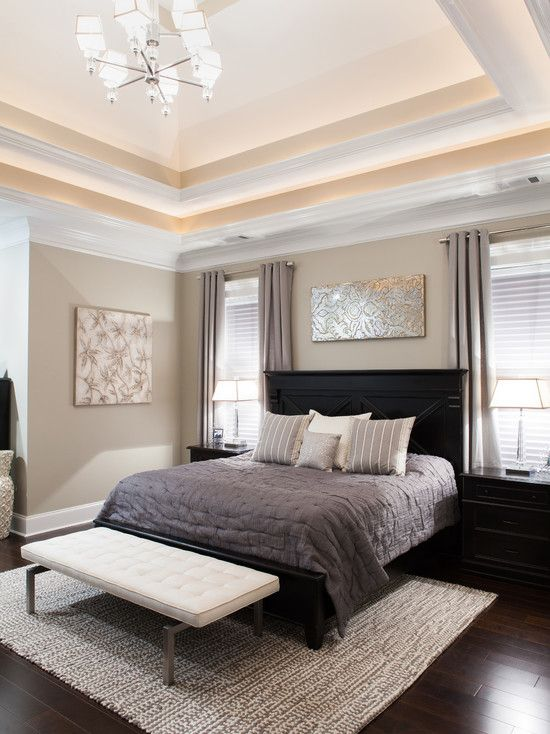 : Transitional Bedroom With Light Brown Wall Paint Color Also Black Modern Bed Divan And Gray Quilt And Soft Color Cushions And Pillows Also White Modern Padded Bench Also Light Gray Curtains And Pendant Light