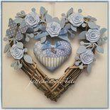 Cuore di vimini tinta naturale decorato con rametti di feltro azzurri ,6 roselline di piquet di cotone azzurre,una farfalla di feltro e cotone a pois ,nastri di canetè sempre azzurri .Al centro un ...