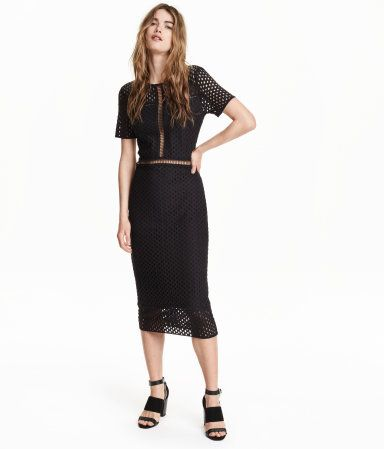 Long, fitted dress in stretch lace with a perforated pattern. Opening at back of neck with button, and short sleeves. Partly lined in jersey.