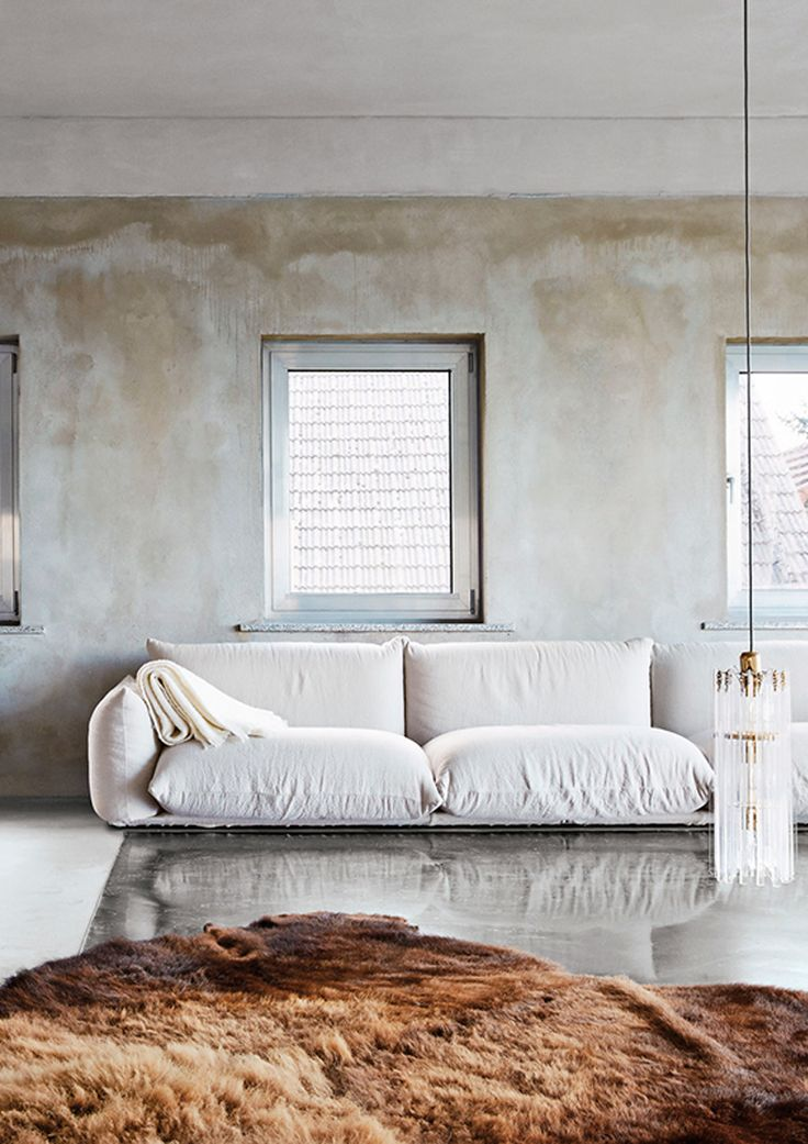 distressed walls, and ivory sofa, and faux fur rug