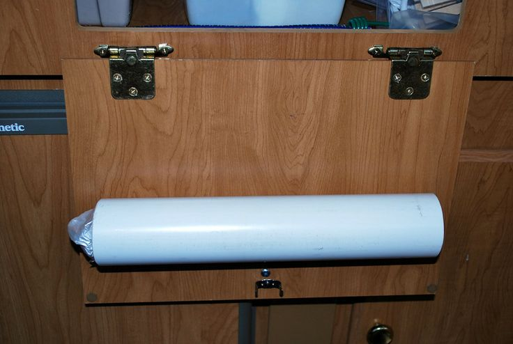 PVC pipe garbage bag holder. Cut out slit in pipe for bags to come out of and either be velcro-ed on to the door or drill holes for hooks.