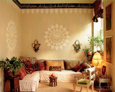 seating area with painted wall medallions and Arabic script in a border around the ceiling.  Wonder what it says?