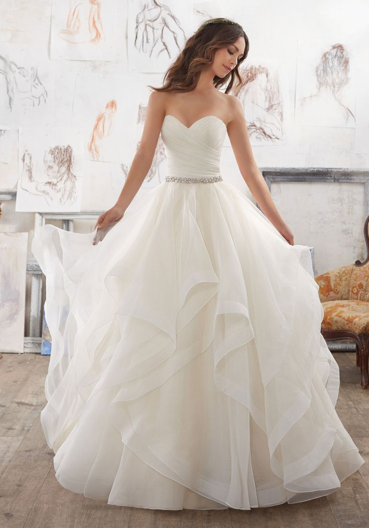 This Dreamy Organza Ballgown Features a Flounced Skirt with Horsehair Trim. Removable Crystal Beaded Satin Belt Included (Crystal Beaded Satin Belt Also Sold Separately as Style #11254). Available in Three Lengths: 55″, 58″, 61″. Colors Available: White, Ivory, Ivory/Light Gold. Find Stores