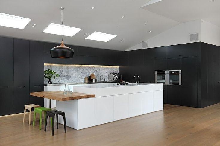 Black kitchen white island. love the way the cabinets continue around the corner.. Herne Bay Villa by Jessop Architects