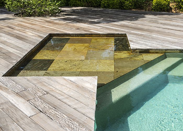 Les pierres qui dallent la plage sont également utilisées sur l'ensemble de la ligne d'eau et font le lien entre le bleu du bassin et le marron grisé du bois