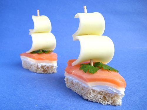 """Канапе """"Кораблики"""".   На хлеб выложить слоями cream cheese, сыр и красную рыбу. Из полученного бутерброда вырезать маленькую лодочку. Паруса сделать из ломтиков сыра, нанизанных на шпажку. Украсить по желанию, например, зеленью."""