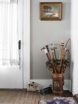 Corner Storage. The owners collection of walking sticks and feather dusters finds a home in an English-leather fire bucket from the late 1800's in the Indiana farmhouse. The midcentury pig doorstop and dachshund boot scraper are both made of cast iron.