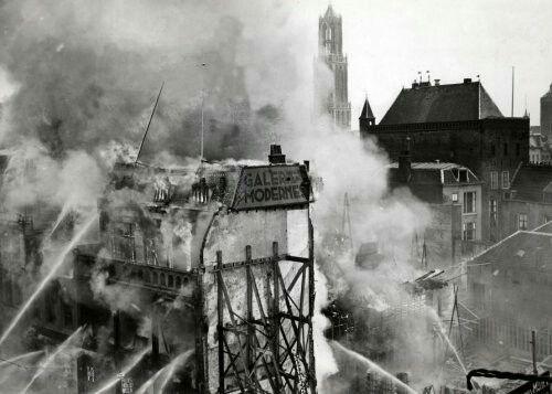 Steden. Uitslaande brand bij de winkel Galerie Modern. Boven de gebouwen stijgt een zwarte rook op. Op de achtergrond is de Domtoren te zien. Utrecht, Nederland, 1939.