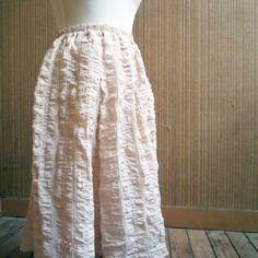 Jupe-jupon à plis creux, griffe personnelle brodée, peut se porter en superposition réalisée pour vous en polyester cloqué coloris