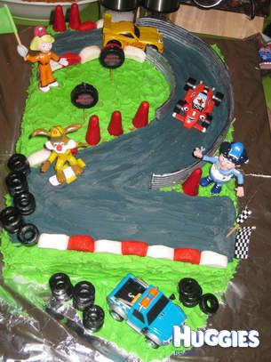 """I wanted to do the number two for my little boys 2nd birthday and decided to make it into a little piece of """"Silverhatch Race track""""as he is a big Roary fan. The cars and Big Chris, Marsha and Flash were bought in packs and then were part of his pressie to keep and are still going strong! The rest was pretty much edible (if you dared!) The cones were actually tips of icecream cones dyed red, the barrier was licorice strap painted with edible silver paint, the red and white road stripes were…"""