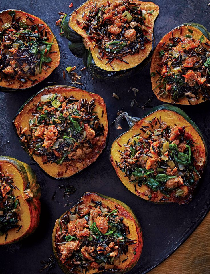 Acorn Squash with Wild Rice Stuffing | This two-for-one dish of wild rice stuffing and roasted acorn squash is a sure crowd-pleaser. You can cut the stuffed halves into quarters so they don't take up as much room on the plate. Wild rice takes about as much time to cook as long-grain brown rice, which you can use as a substitute. You can also make the rice ahead and refrigerate. Reheat with a splash of water before adding to the sausage mixture.