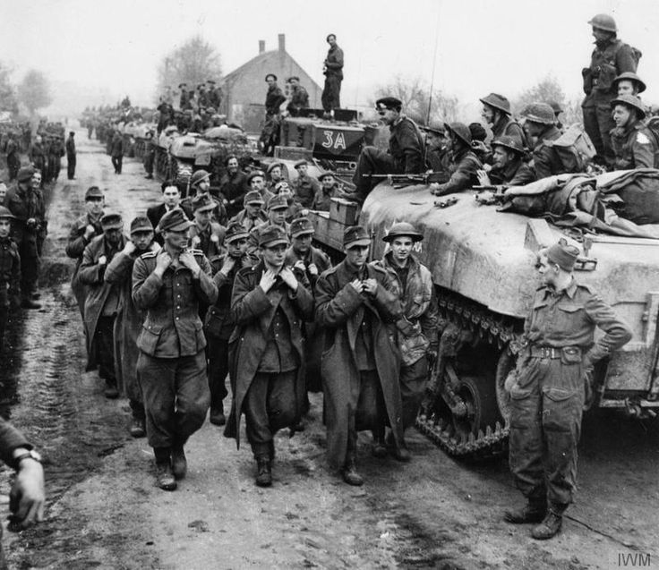 German prisoners are led past Churchill tanks and Kangaroo infantry carriers near Tilburg, 28 October 1944.