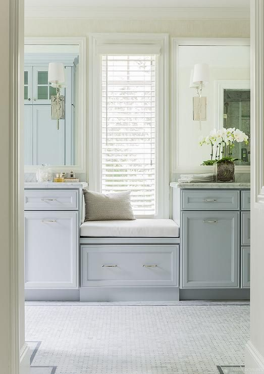 Gorgeous bathroom features a a built-in window seat with drawer flanked by separate vanities fitted with blue gray cabinets adorned with nickel hardware topped with gray and white marble under white beveled vanity mirror illuminated by Hudson Valley Lighting Glenford Sconces alongside marble basket weave tiled floor accented with gray border tiles.