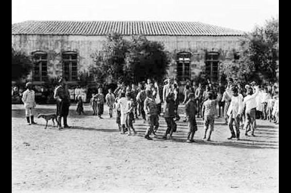 Η αυλή του Δημοτικού σχολείου στον Δραπανιά, με τα παιδιά να χαίρονται το παιχνίδι τους. 1911. Fred Boissonas. Σχόλιο Μανώλη Μανούσακα.