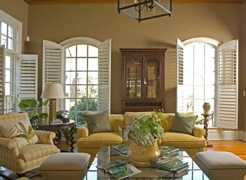 These tall arched living room windows have plantation shutters (shutters with individual louvers that are 2 1/2 to 4 1/2 inches wide) with the exact same arched top.    Style tip: Don't be scared to use different styles of shutters on different windows in the same room. In this picture, full-height shutters mix with partial-height shutters.