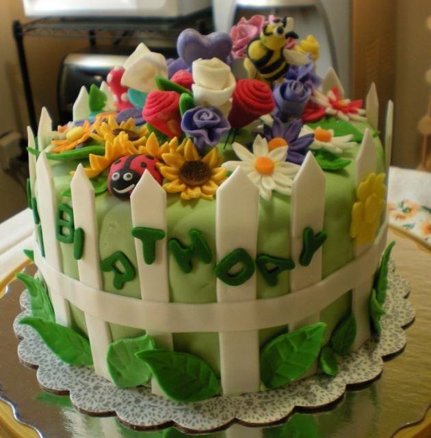 Garden theme birthday cake with white picket fence, ladybug, and bee.
