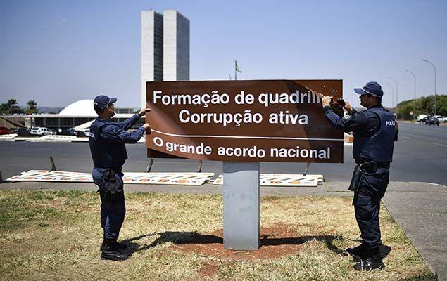 Policiais retiram placa com frases alusivas à corrupção colocada por manifestantes em frente ao Congresso Nacional, nesta segunda