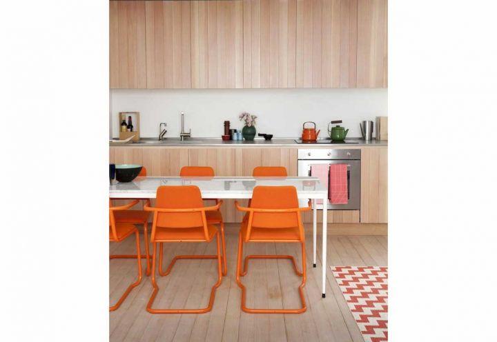 Parquet in legno chiaro in tinta con i mobili della cucina su misura nel living dell'abitazione curata da Studiomama. Siamo nell'East End di Londra