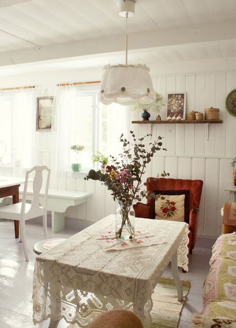 Floral arrangement in jar at the table and on the shelf and potted plants in the window.