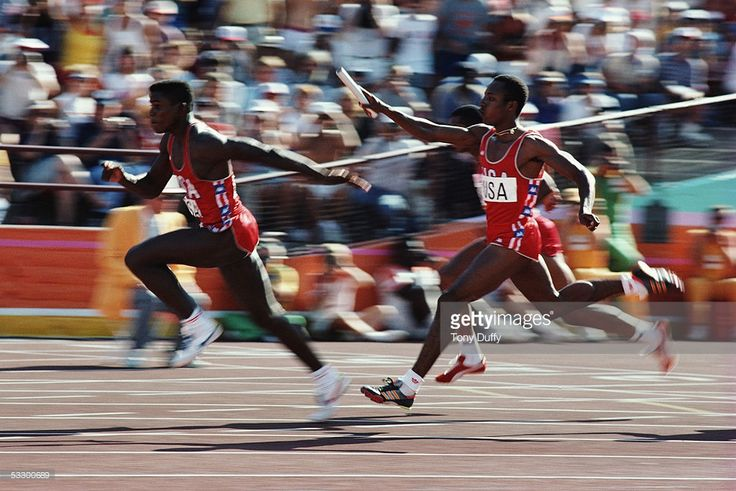 Carl Lewis of the USA receives the baton from team mate Calvin Smith as he anchors the USA team to victory in a new world record time of 37.83 seconds in the 4 x 100m relay during the 1984 Olympic Games at the Colliseum Stadium on August 11, 1984 in Los Angeles.