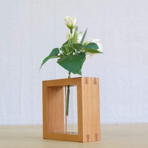 山桜のフラワーベースをお送りいたします。天秤挿しで枠組み、製作しました。試験管、一本付属します。4枚目の写真は、左からアサダ、ウォールナット、山桜×2、アサダ※写真の商品はサンプル品です。個々によって木目等異なります。材:山桜大きさ:102ミリ×105ミリ×42ミリ仕上げ:オイルフィニッシュ