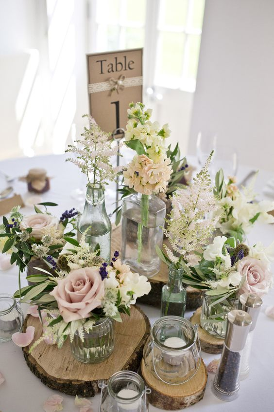 centrepiece of rustic tree slices with jars of pink flower stems