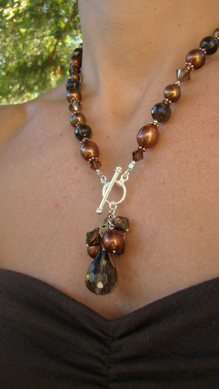 Faceted smokey quartz, brown rice fresh water pearls, smoked topaz satin Swarovski crystals and copper with brass and copper leaves. Finished with sterling silver. Style 2514-N1