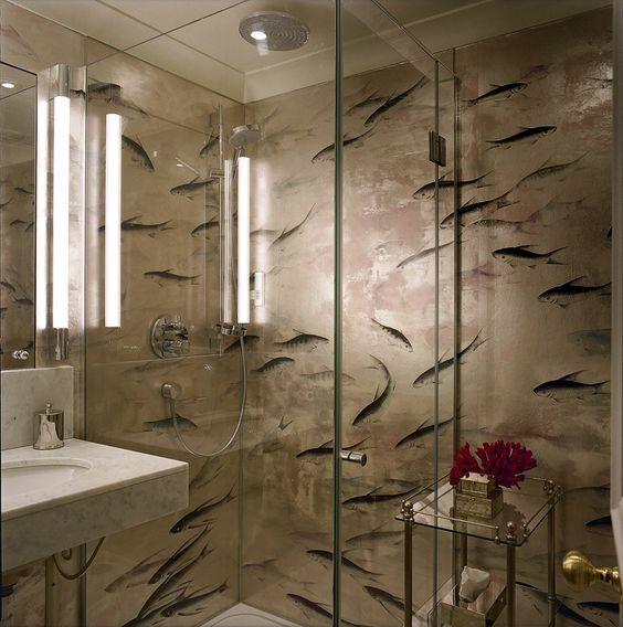 Photos On The bathroom simply posed of a glass shower enclosure and a basin is lined with Fishes de Gournay wallpaper treated to resist moisture