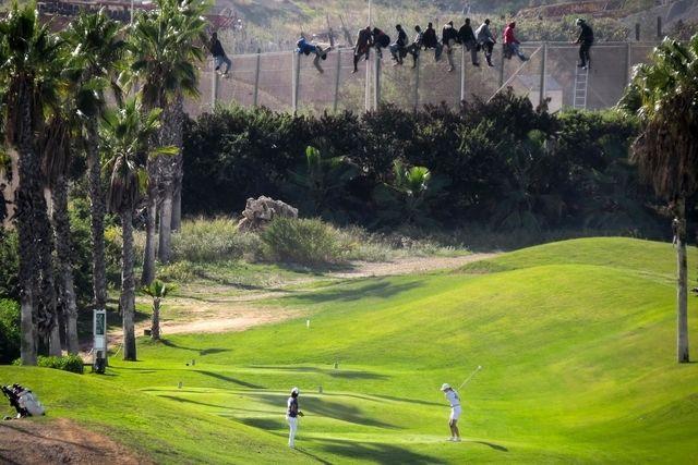 Fremde Welten: Während eine Golferin in Melilla ihren Schlag macht, versuchen afrikanische Flüchtlinge, über den Grenzzaun zu klettern. (22. Oktober 2014)
