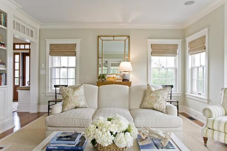 Beautiful living room features walls painted light khaki, Benjamin Moore Nantucket Breeze, framing sash windows dressed in woven shades on either side of an oak chest topped with a happiness jar table lamp below a gilt beveled mirror flanked by a pair of antique chairs. An English rolled arm sofa stands in front of the chest topped with a pair of green paisley pillows beside a green striped rolled arm chair on casters atop a bound sisal rug across from a white coffee table laden with books
