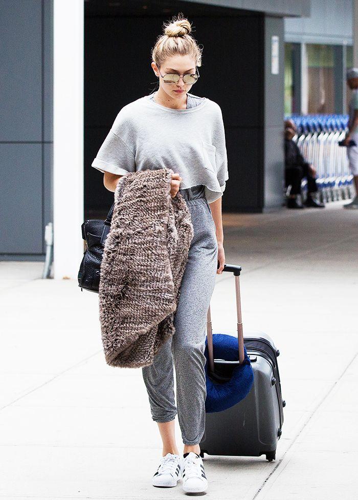 Gigi Hadid wears a gray top, gray sweatpants, Adidas sneakers, aviator sunglasses, and a furry blanket