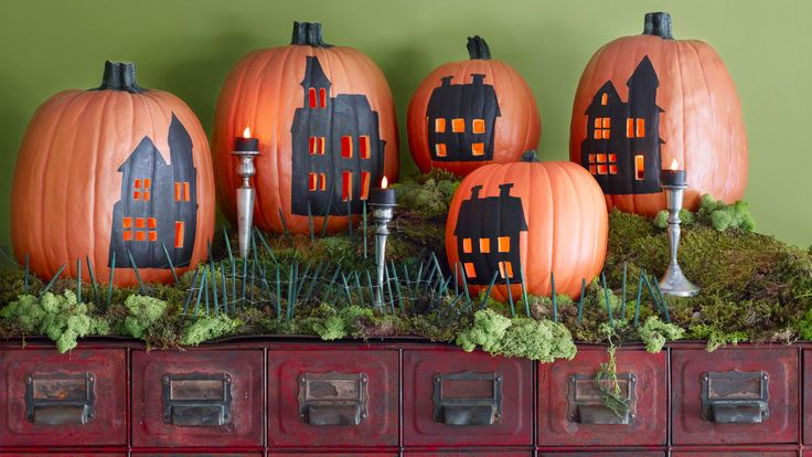 A passel of halloween pumpkins provides the backdrop for a spooky village scene.